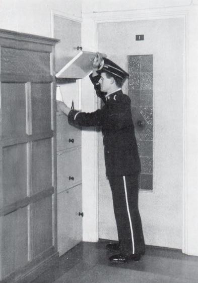 A uniformed porter leaves bottled milk for a resident